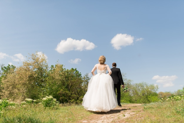 O noivo e a noiva voltam para a campina