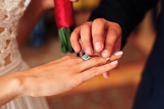 O noivo e coloca uma aliança no dedo da noiva