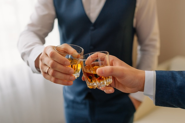 O noivo e o padrinho bebendo um uísque, comemorando o dia do casamento. mãos de homem segurando copos com álcool e brindar. grupo de homens torcendo e tilintando com bebidas na recepção do casamento