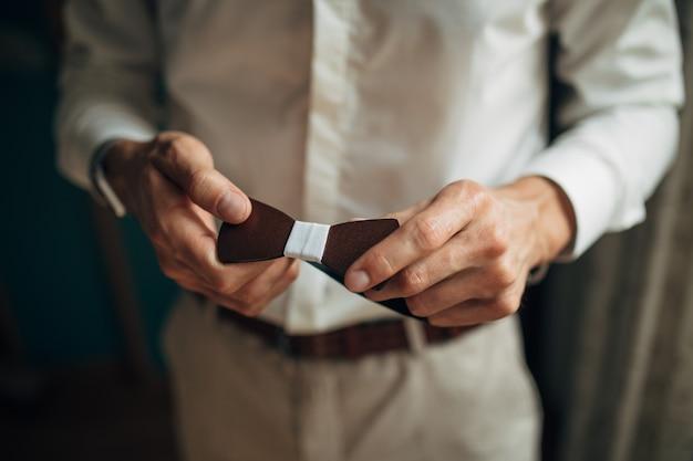 O noivo em um colar branco, consertando sua gravata borboleta