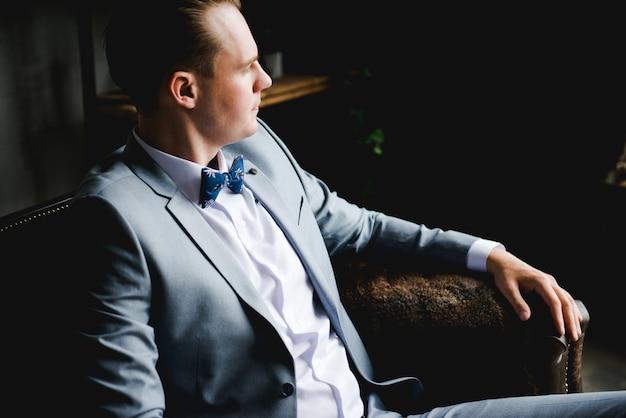 O noivo em um terno cinza, camisa branca e gravata-borboleta está sentado em um sofá de couro marrom.