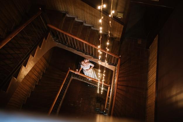 O noivo em um terno e a noiva em um vestido de noiva estão de pé em uma escada de madeira