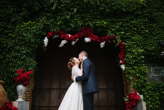 O noivo em um terno e a noiva em um vestido de noiva estão de pé no arco de casamento na cerimônia de casamento