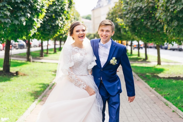 O noivo em um terno estiloso abraça a noiva e olha para a câmera caminhando no parque