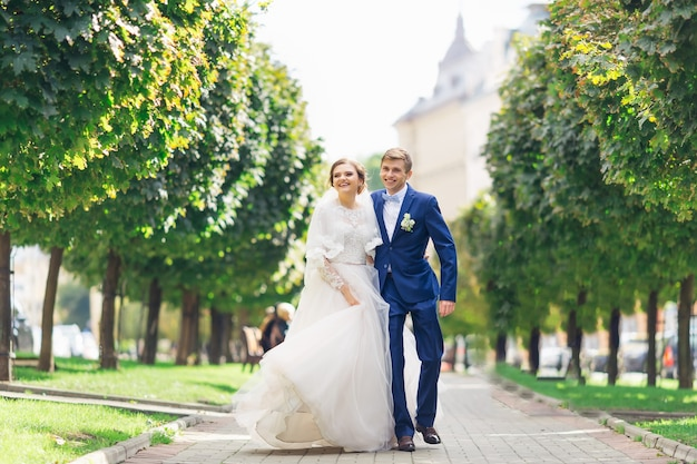 O noivo em um terno estiloso abraça a noiva e olha para a câmera