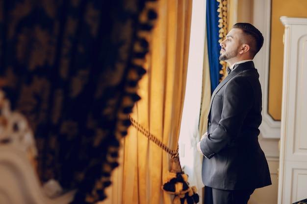 O noivo em um terno preto e uma barba fica em uma sala perto da janela