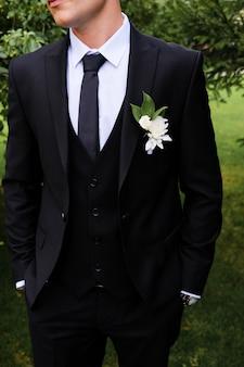 O noivo em uma camisa branca, gravata, terno preto ou azul escuro.