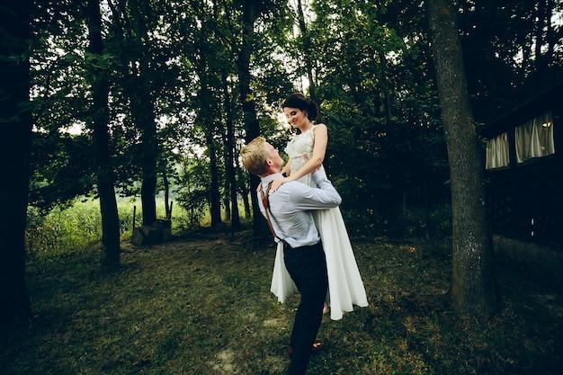 O noivo ergueu a noiva nos braços no parque