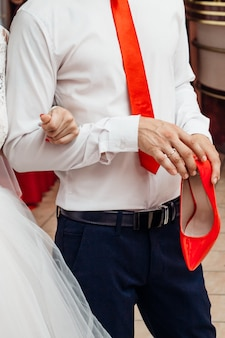 O noivo está segurando o sapato vermelho da noiva