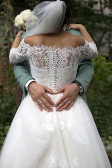 O noivo faz o coração com as mãos no vestido da noiva. recém-casados abraçando
