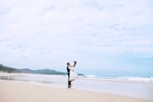 O noivo levanta a noiva nos braços em uma praia tropical