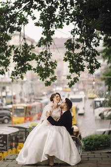O noivo na cadeira de rodas prende a noiva de joelhos que senta-se fora no parque