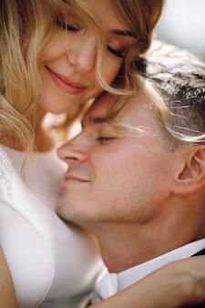 O noivo no smoking preto abraça a noiva impressionante macia enquanto estão