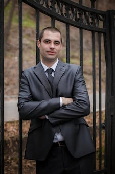 O noivo ou o homem ficar perto do portão de ferro no parque outono