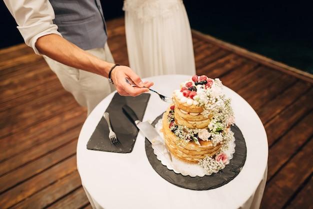 O noivo pega um pedaço de bolo com um garfo para dar à noiva em um banquete de casamento