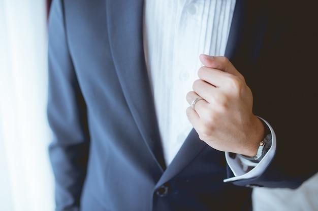 O noivo pegou seu terno azul que seu dedo tem uma aliança de casamento