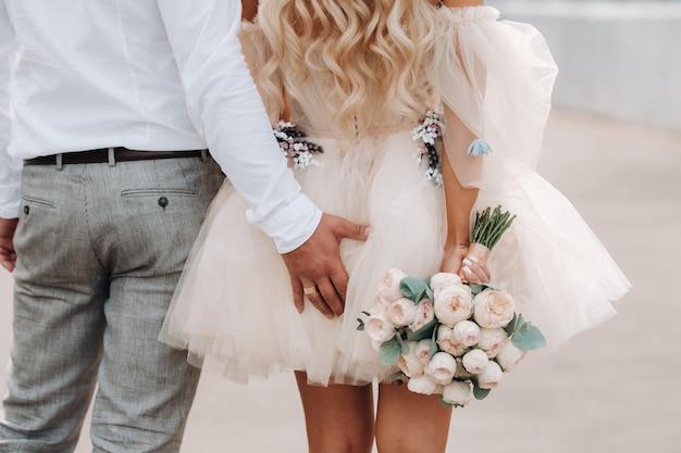 O noivo põe a mão atrás da noiva. a noiva em um vestido curto está segurando um buquê nas mãos por trás