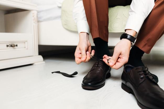 O noivo se senta na cama e usa sapatos de casamento