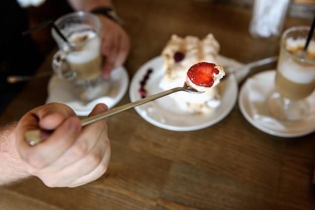 O noivo segura a colher de merengue com morangos no fundo da mesa com café