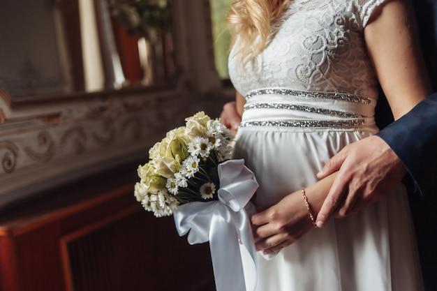 O noivo segura a noiva grávida pelas mãos.