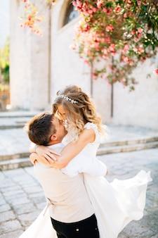 O noivo segura a noiva nos braços e beija no local ao lado da antiga igreja em prcanj