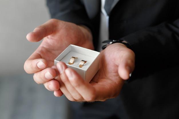 O noivo segura as alianças na palma da mão.