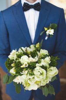 O noivo segura o buquê de flores
