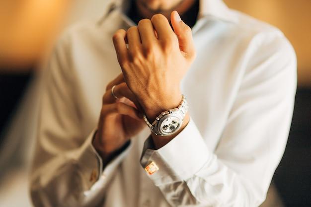 O noivo segura seu relógio. casamento em montenegro