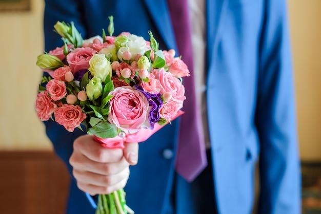 O noivo segura um buquê de casamento