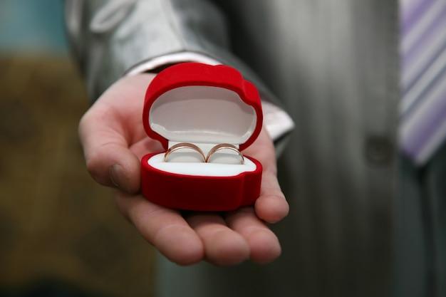 O noivo segura uma caixa com alianças de ouro de perto