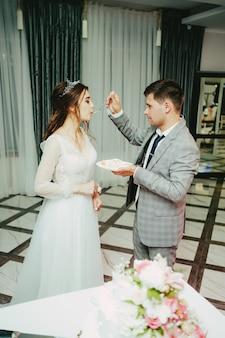O noivo serve a noiva com bolo