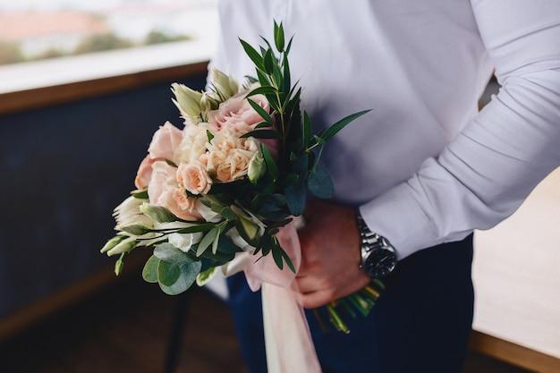 O noivo tem um buquê nas mãos dele