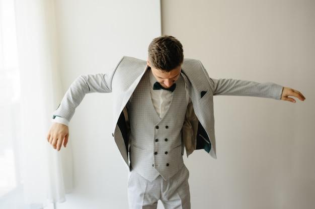 O noivo veste a jaqueta.