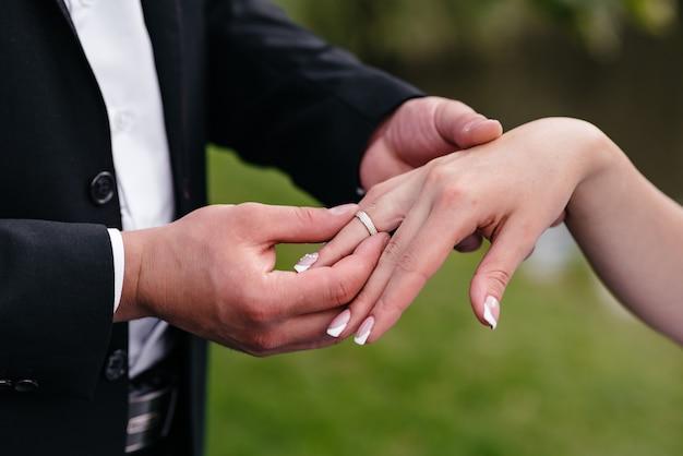 O noivo veste o anel de casamento da noiva na mão.