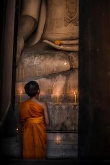 O novato está olhando para a grande imagem de buda na igreja para orar pelo respeito à religião.