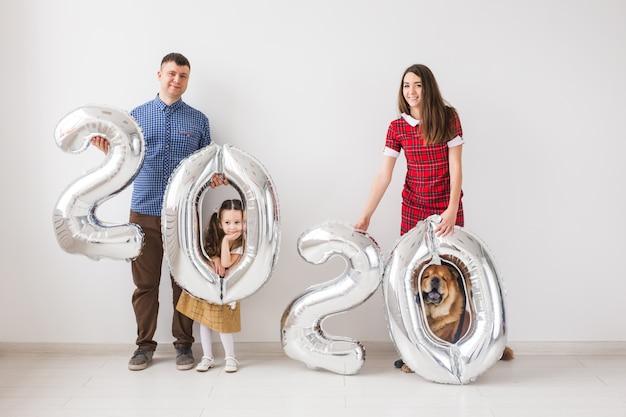 O novo ano 2020 está chegando conceito - a família feliz com cachorro está segurando números coloridos prateados dentro de casa.