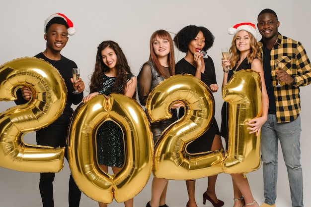 O novo ano de 2021 está chegando grupo de jovens alegres com gorros de papai noel e números dourados