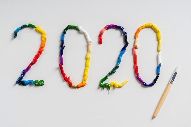 O número 2020 é pintado em tela branca com tintas a óleo brilhantes. vista superior close-up.