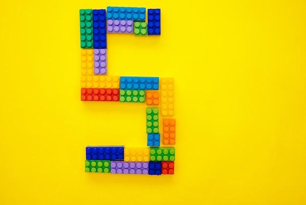 O número cinco do construtor multicolorido das crianças em um fundo amarelo. espaço vazio para o texto. data de feriado.
