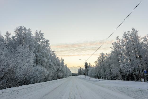 O número da estrada 496 cobriu com neve pesada na estação do inverno em lapland, finlandia.