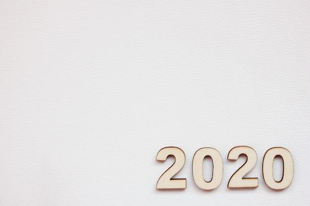 O número do ano 2020 novo é alinhado com números de madeira em um fundo branco.