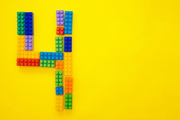 O número quatro do construtor multicolorido das crianças em um fundo amarelo. espaço vazio para o texto. data de feriado.