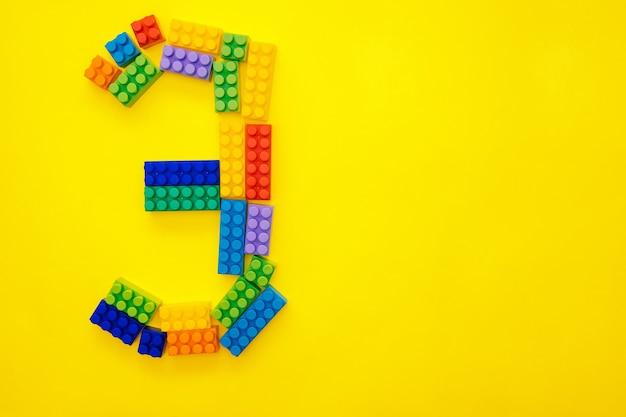 O número três do construtor multicolorido das crianças em um fundo amarelo. espaço vazio para o texto.