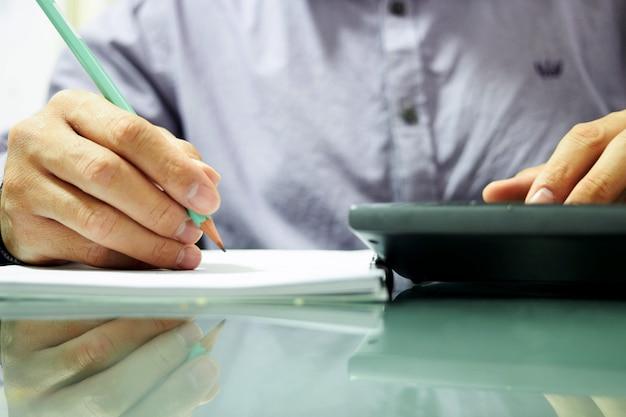O oficial uniforme trabalha em notas da contabilidade com lápis, caderno e calculadora no conceito da economia ou do imposto