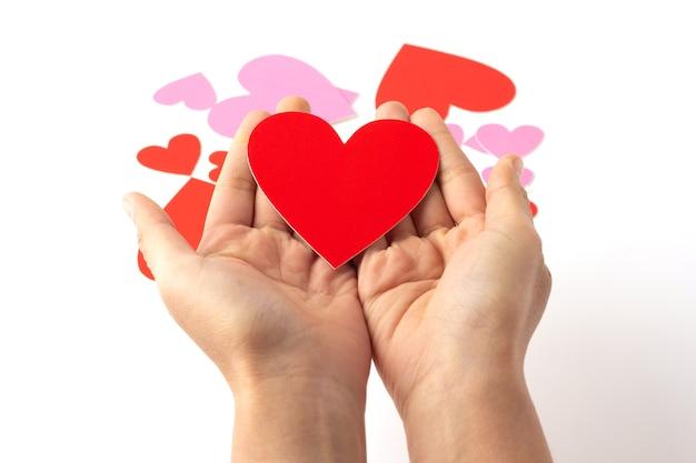 O ofício de papel em forma de coração vermelho coloca à mão isolado, o ofício de papel em forma de coração vermelho e rosa está espalhado, o conceito de amor e o dia dos namorados.