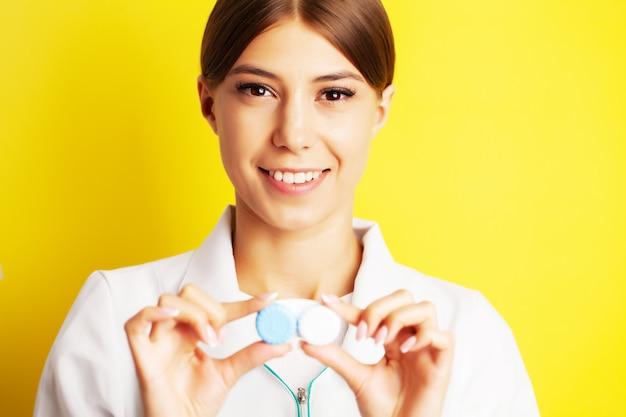 O oftalmologista segura um recipiente com lentes de contato próximas aos olhos