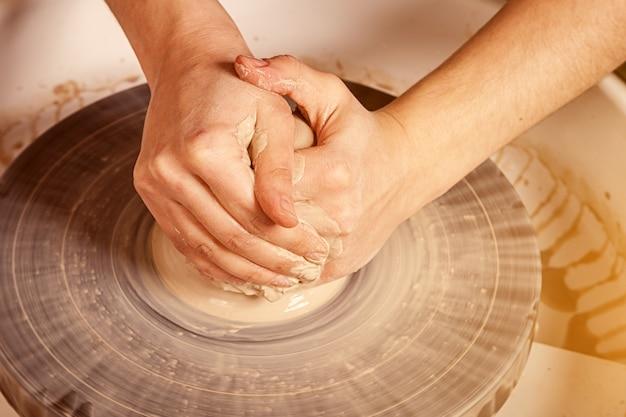 O oleiro da mulher esculpe uma argila