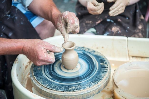 O oleiro faz pratos de cerâmica na roda de oleiro. o escultor na oficina faz o close up de um produto de argila. mãos do oleiro.