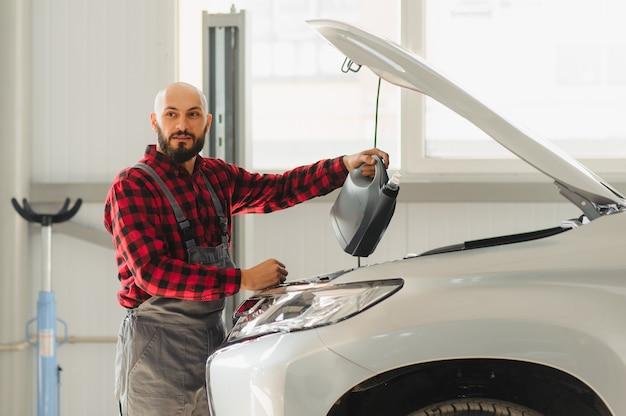 O óleo é substituído no motor de um carro por um mecânico qualificado