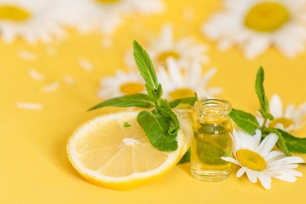 O óleo essencial na garrafa de vidro com camomila fresca floresce, tratamento da beleza.